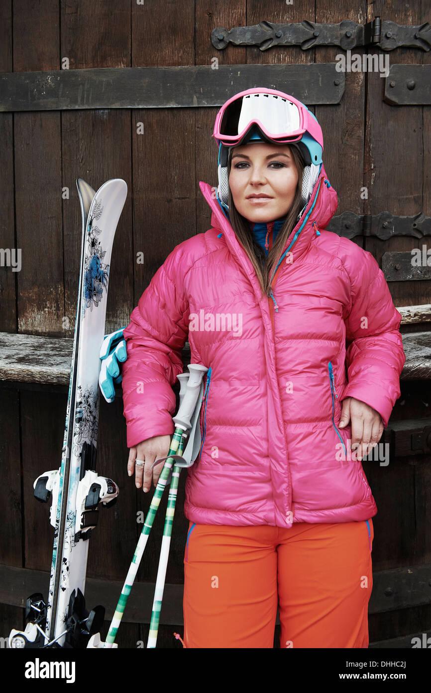 Junge Frau lehnt sich gegen die Tür, mit Ski und Skiausrüstung Stockbild
