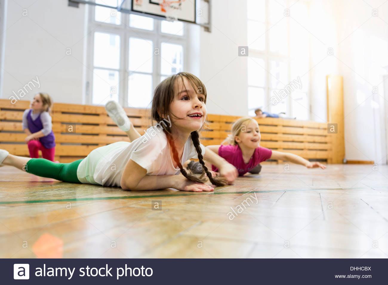 Mädchen liegend auf Vorderseite im Sportunterricht, stretching Stockbild