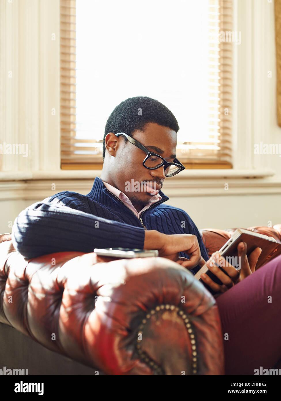 Junger Mann auf Sofa lesen Stockbild