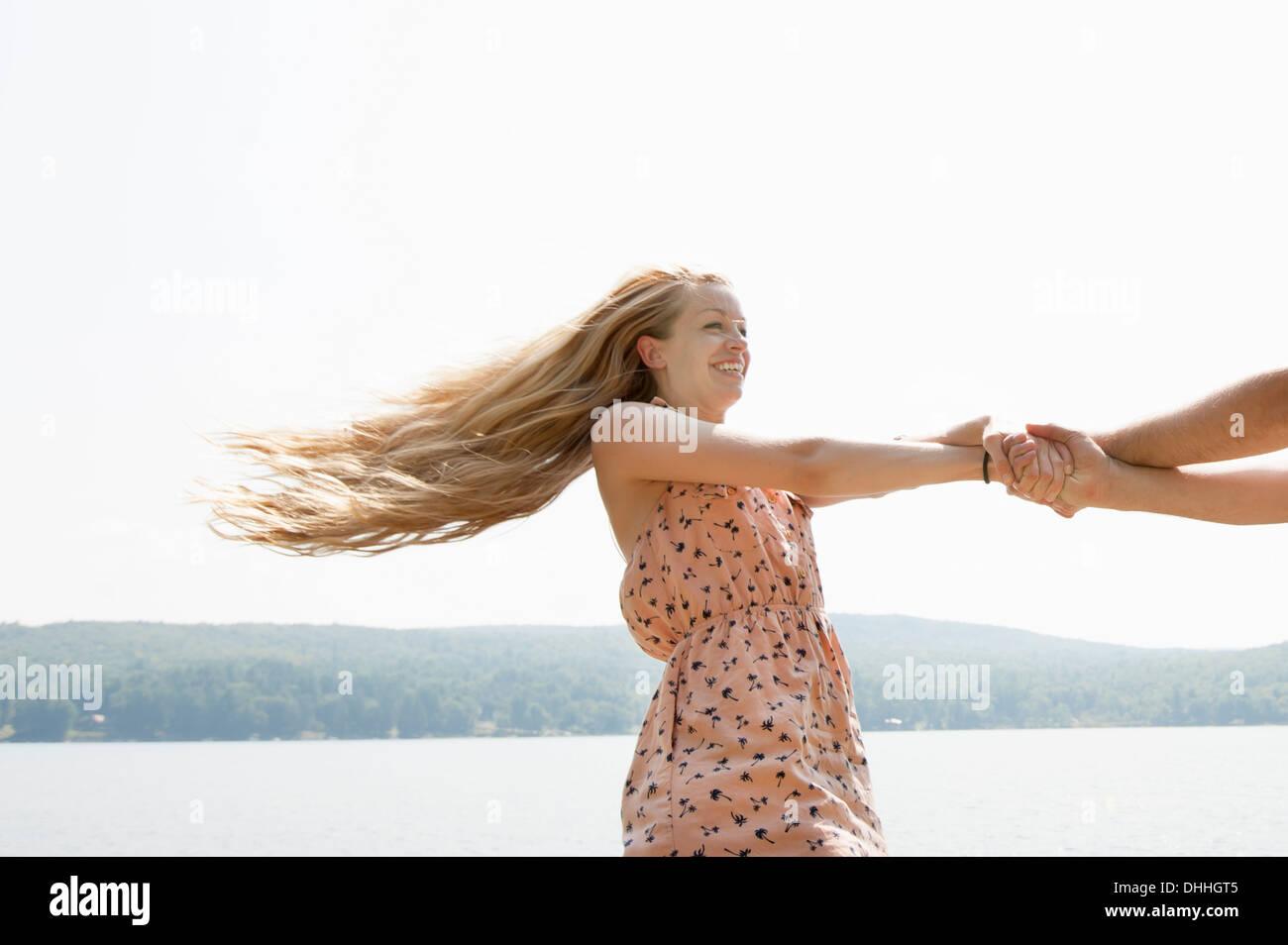 Junges Paar Hand in Hand, Frau mit langen blonden Haaren Stockbild
