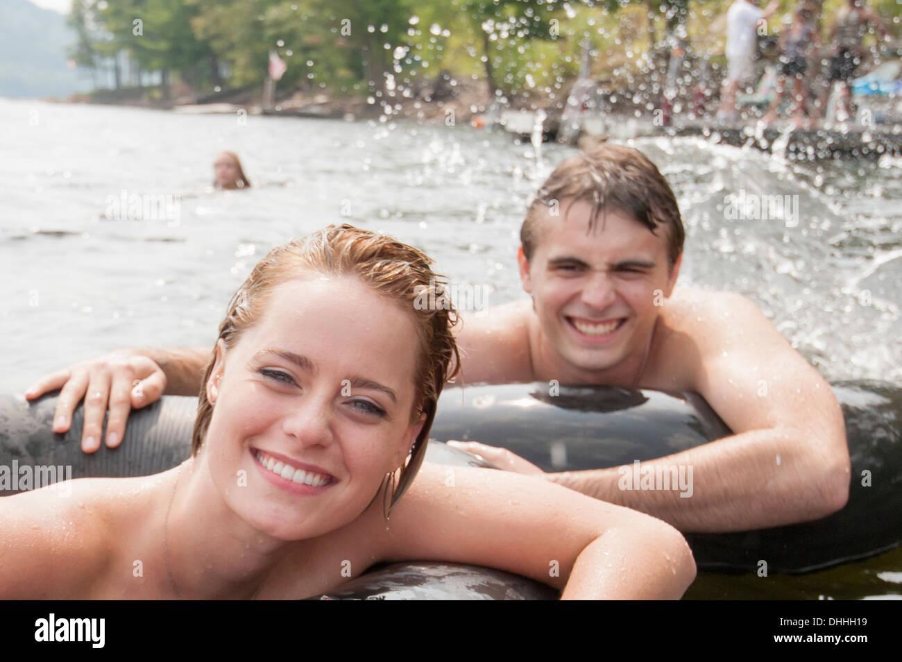 Junges Paar im aufblasbaren Ringen schweben Stockbild