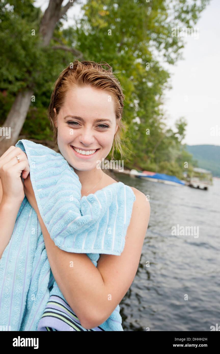 Junge Frau mit nassen Haaren halten Handtuch Stockbild