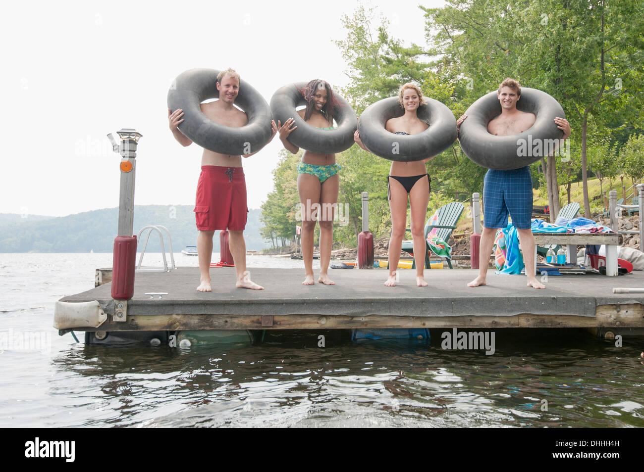 Freunde am Hafenkai mit aufblasbaren Ringen um Hals Stockbild