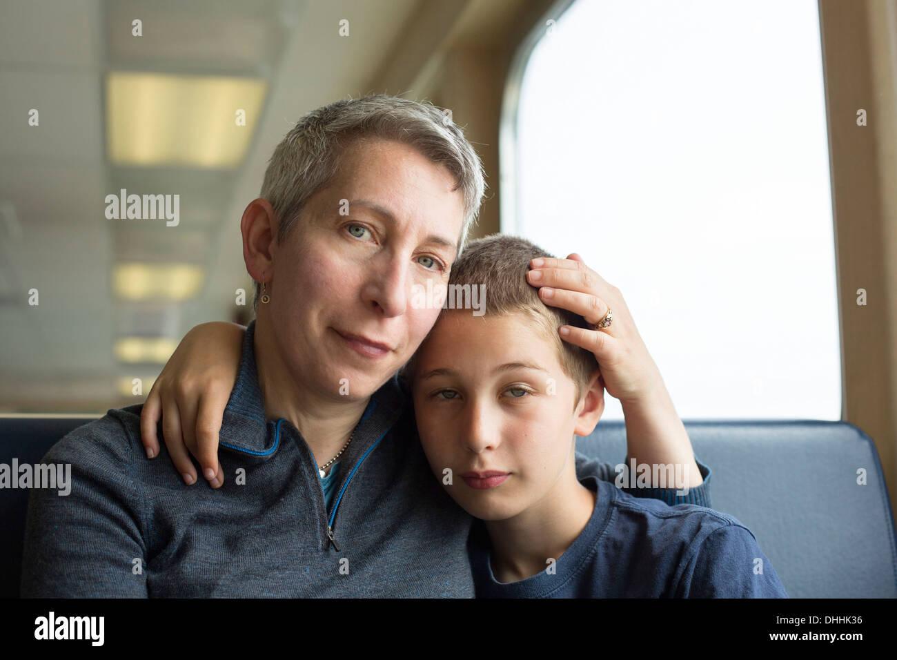 Mutter und Sohn sitzen zusammen mit Arm um Stockbild