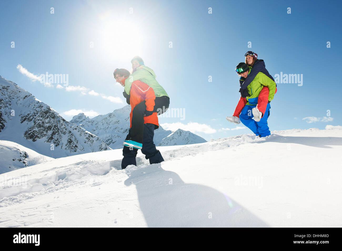Freunde geben Schweinchen im Schnee, Kühtai, Österreich den Rücken Stockbild