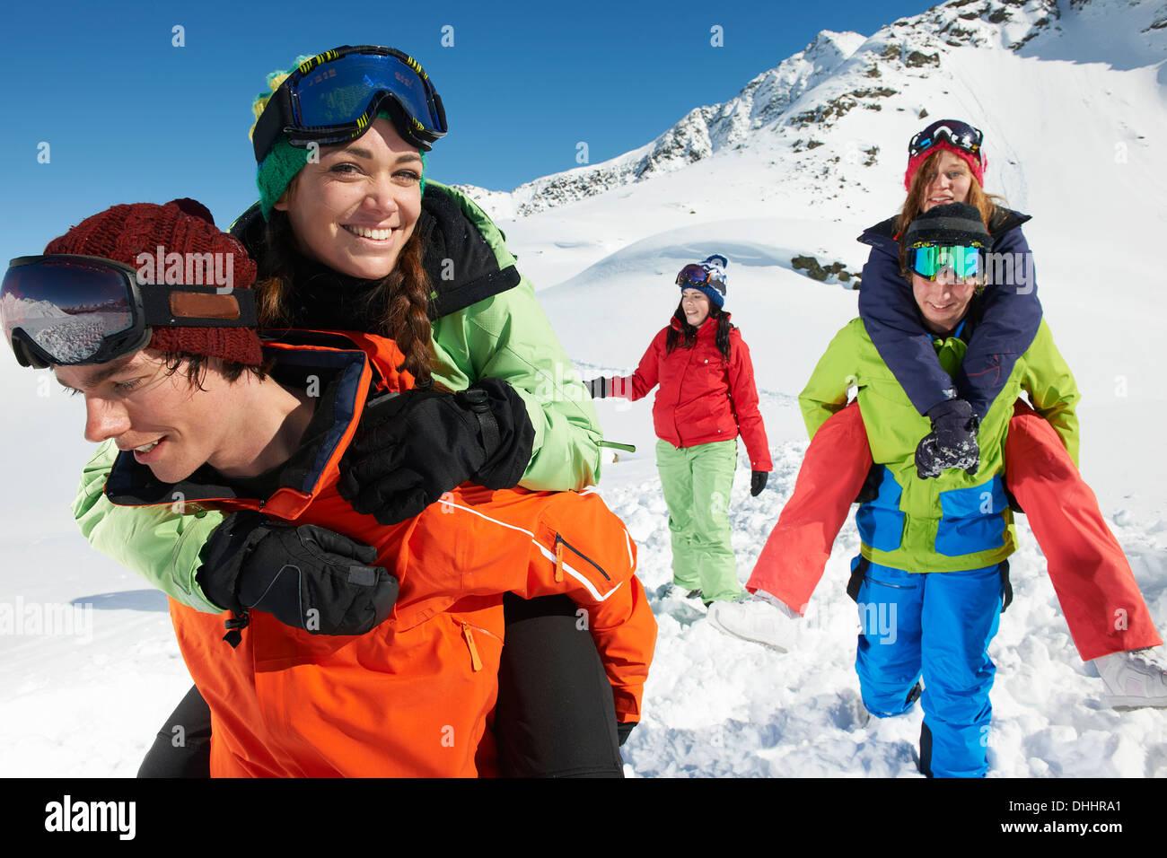 Männer geben Frauen Schweinchen im Schnee, Kühtai, Österreich sichert Stockbild
