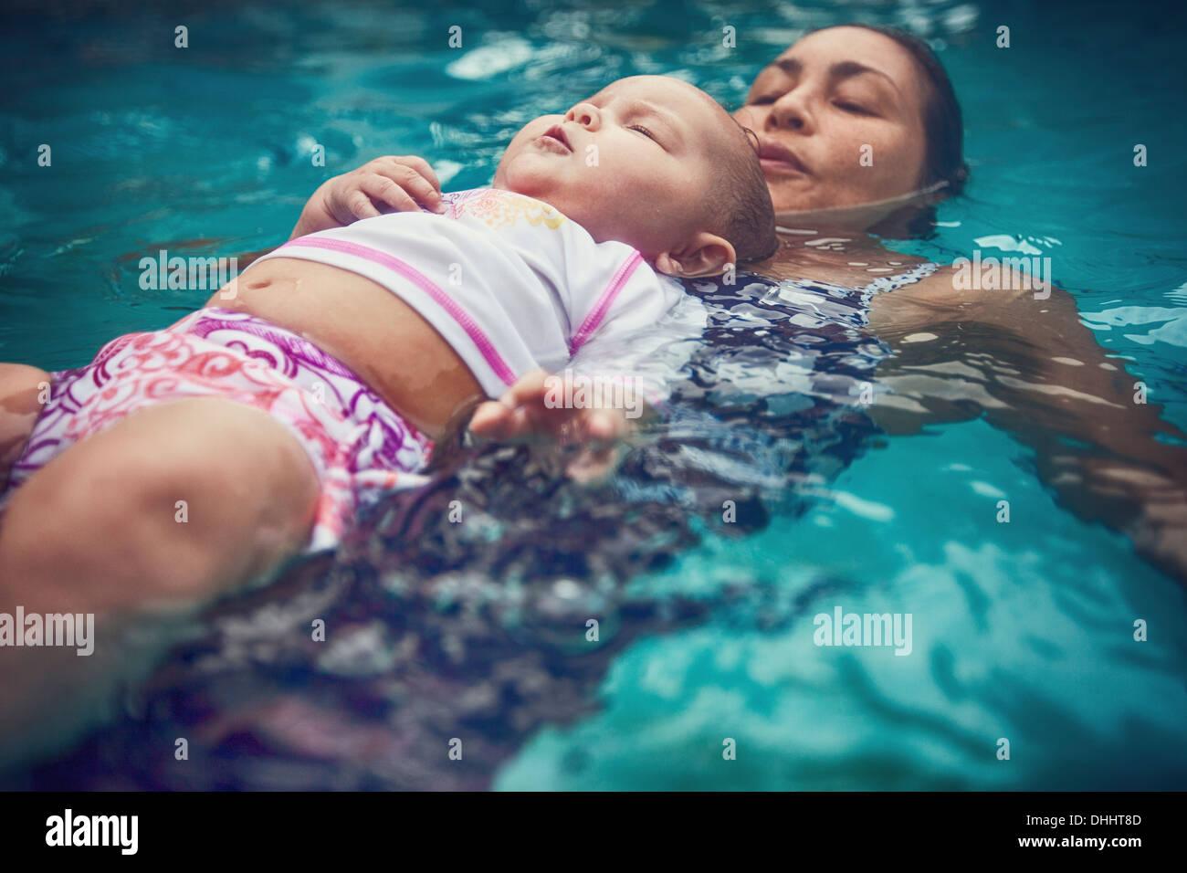 Mutter und Baby Tochter am Rücken im Wasser schweben Stockbild