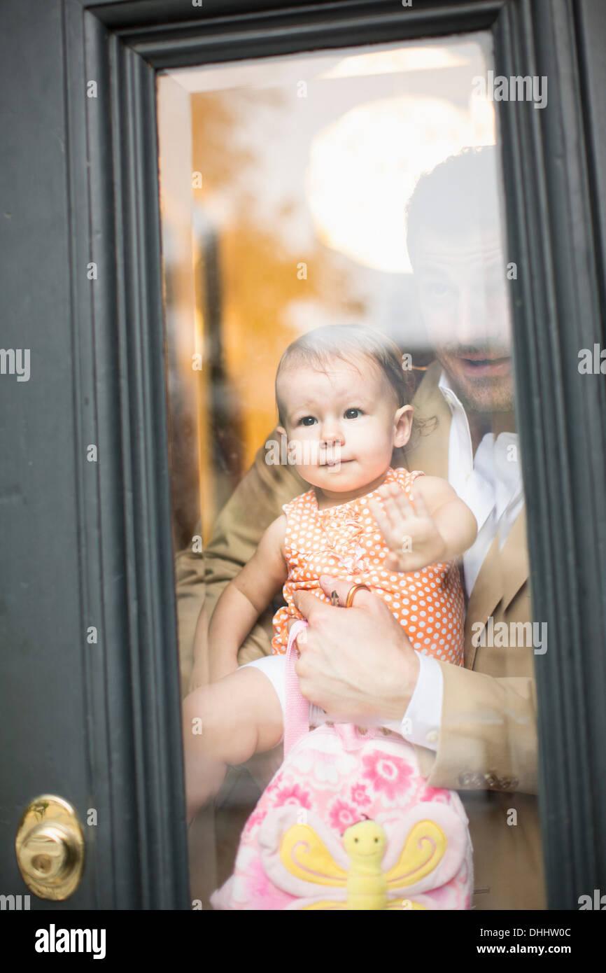 Mann halten Baby Blick durch die Haustür Stockbild