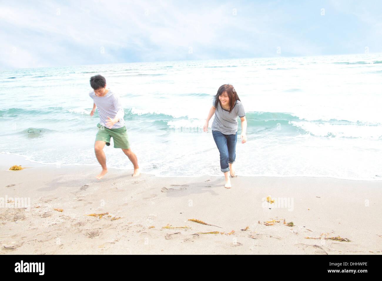 Junges Paar auf der Flucht vor der Flut Stockbild