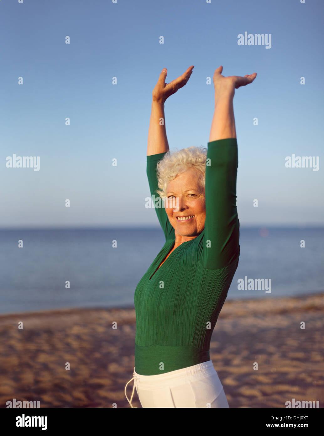 Porträt der gesunde ältere Frau praktizieren Yoga am Strand mit Exemplar. Passen alte kaukasische Frau trainieren im Freien bleiben. Stockbild