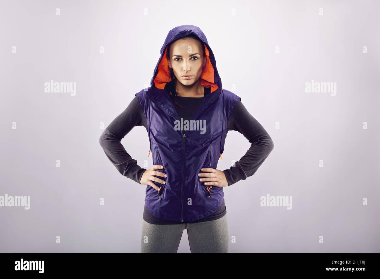Porträt von zuversichtlich Sportlerin stehend mit den Händen auf den Hüften vor grauem Hintergrund mit Exemplar. Stockfoto