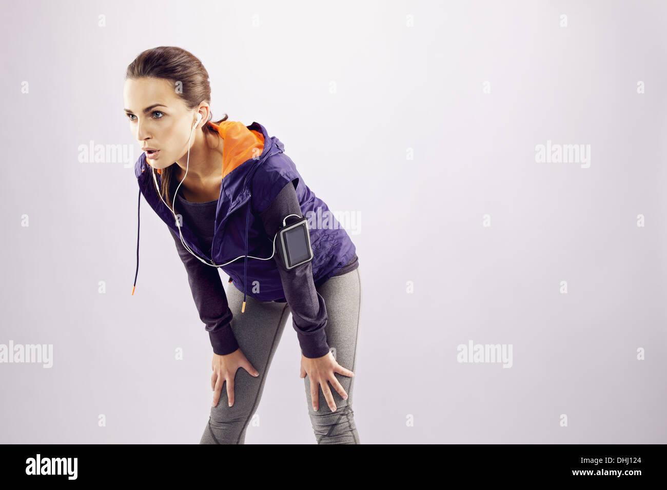 Junge weibliche Läufer mit den Händen auf die Knie. Müde junge Frau ruht nach dem Joggen auf grauem Hintergrund mit vielen Textfreiraum Stockbild