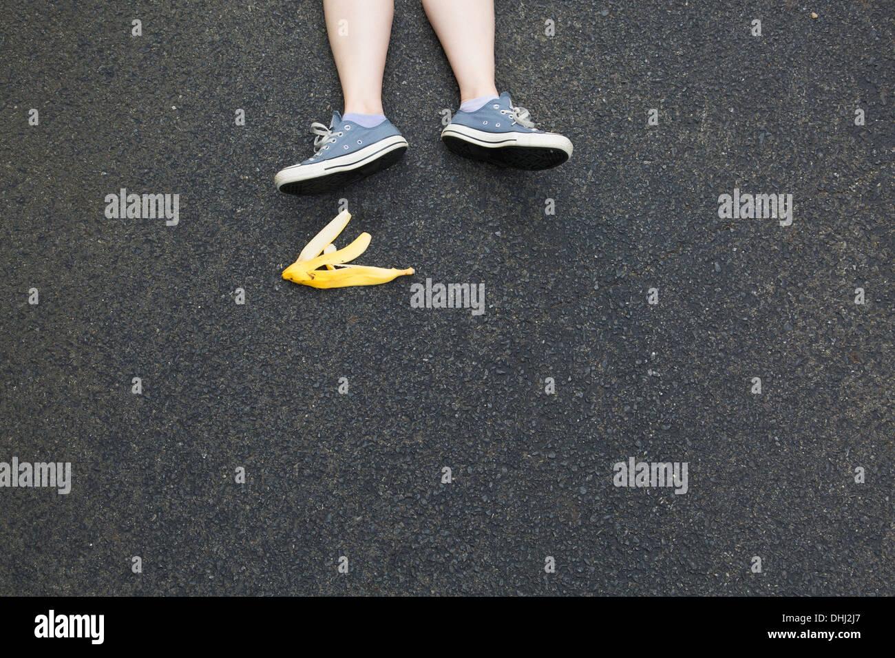 Paar Beine und Bananenschale auf Asphalt Stockbild