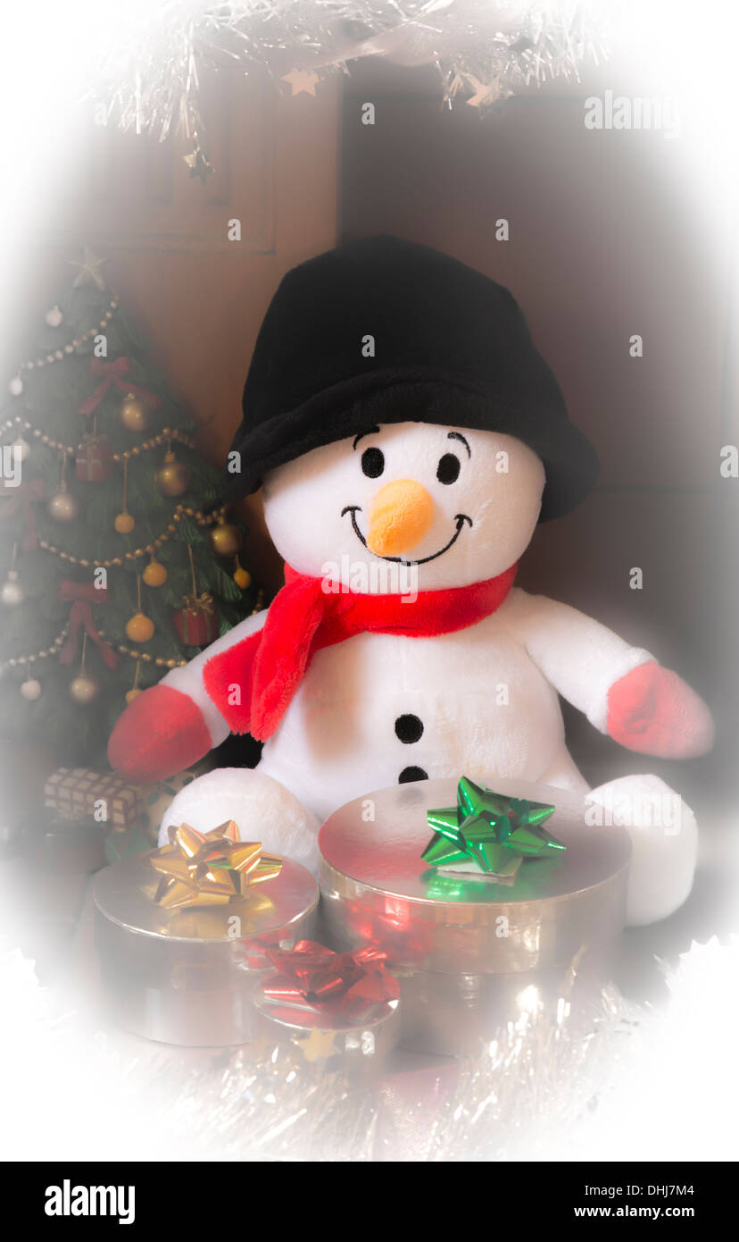Ein Plüschtier Schneemann sitzt neben Weihnachtsgeschenke Stockfoto ...