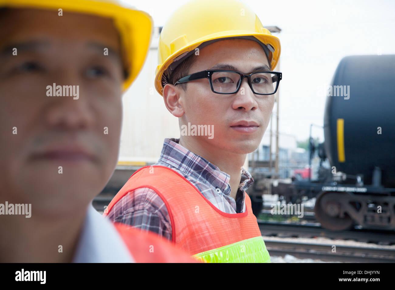 Ernst Ingenieur in Schutzkleidung Blick in die Kamera draußen vor Eisenbahnschienen Stockfoto