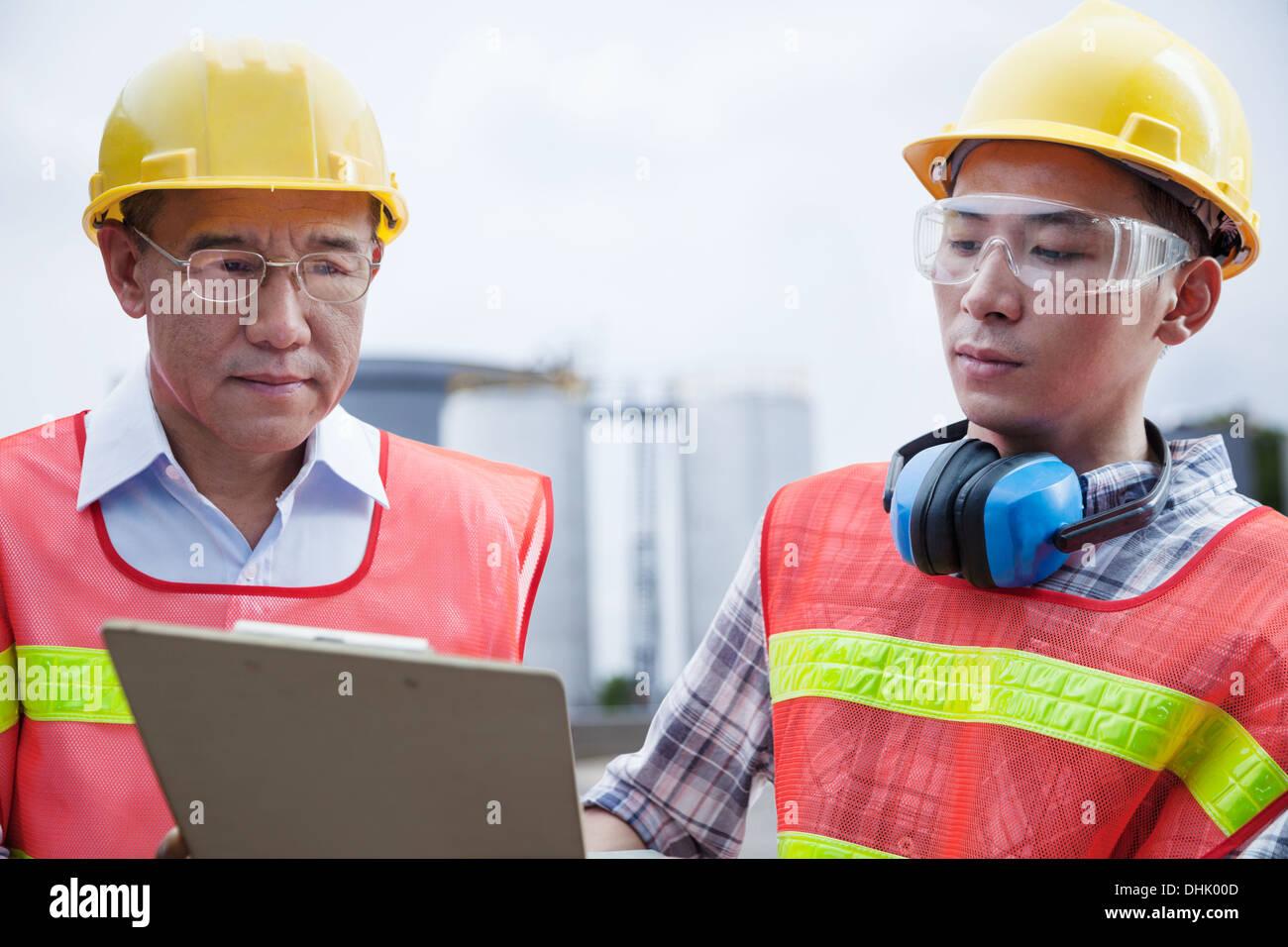 Zwei Ingenieure in Schutzkleidung blickte auf eine Zwischenablage außerhalb einer Fabrik Stockfoto