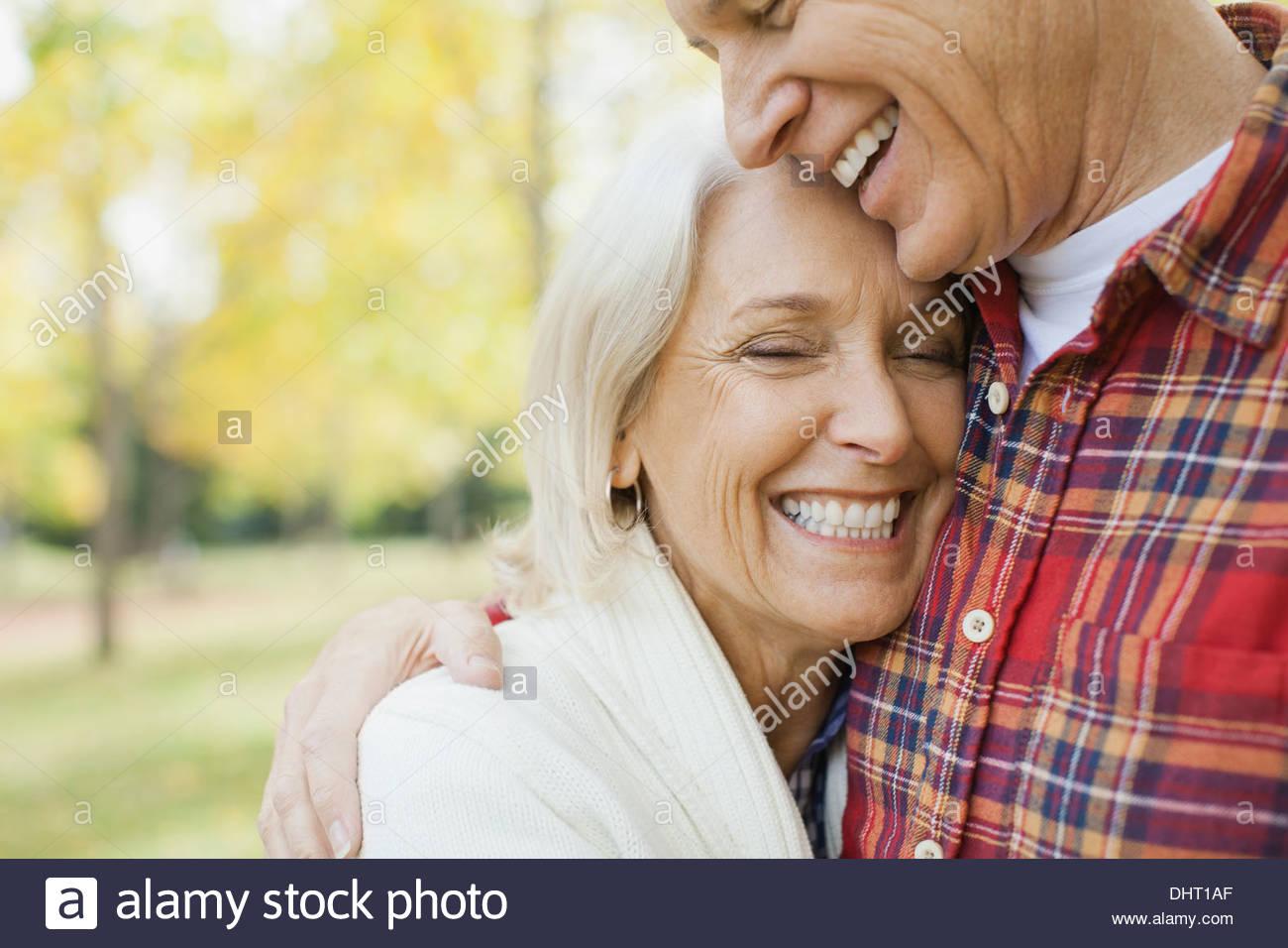 Reifen Mann umarmt Frau im Park zu lieben Stockbild