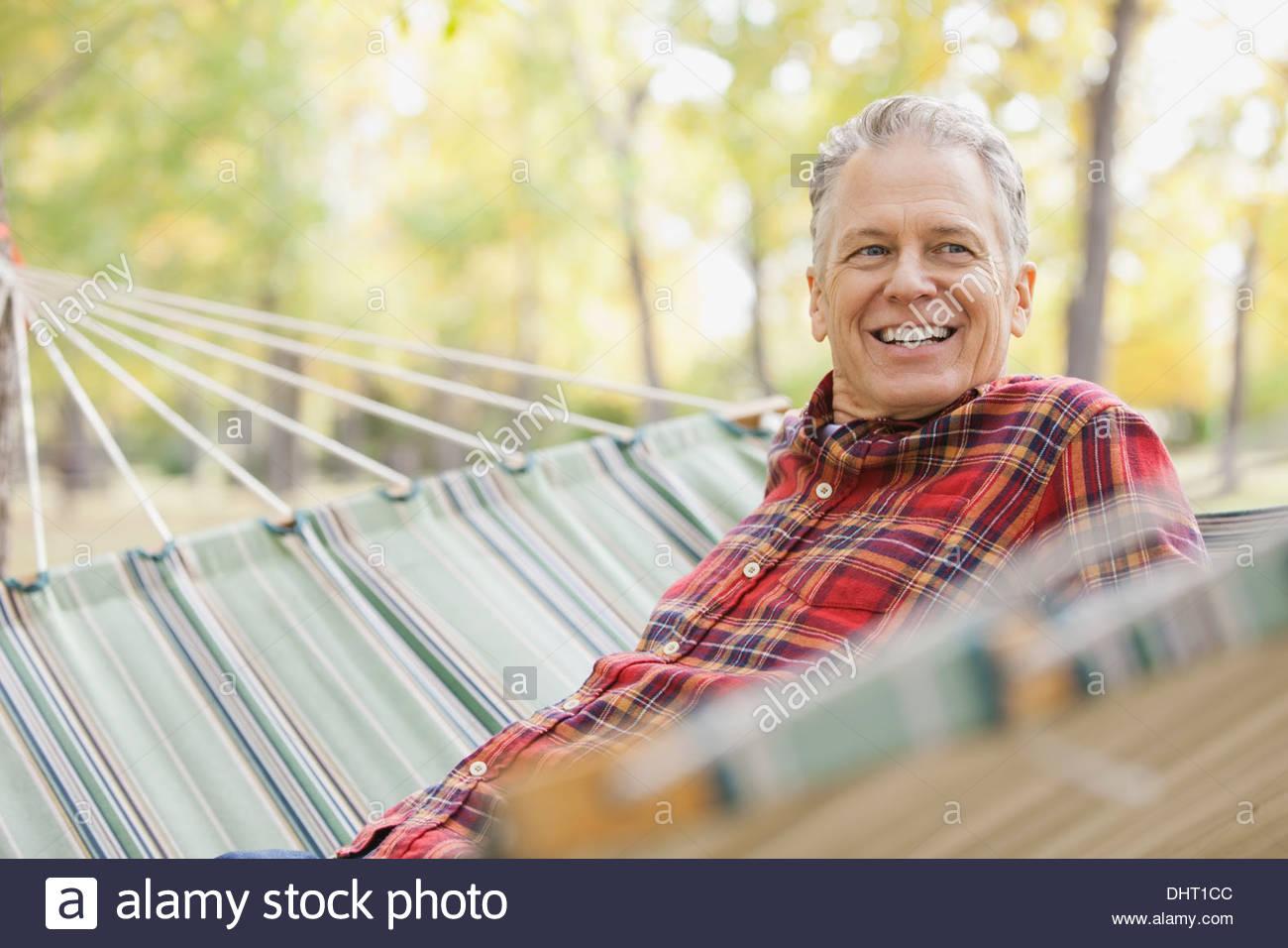 Glücklich reifer Mann sitzt in der Hängematte im park Stockbild