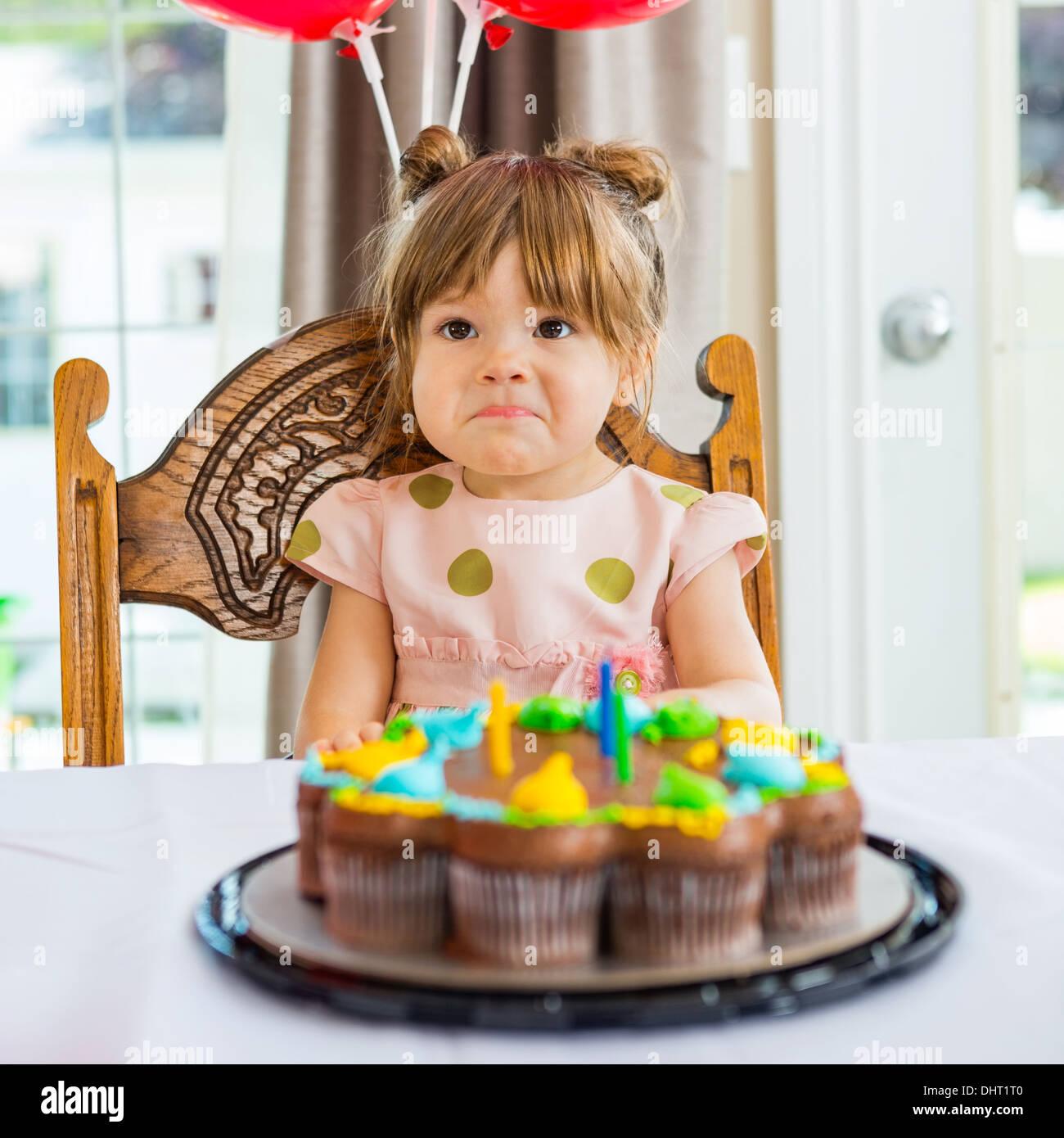 Geburtstagskind sitzt vor Kuchen Stockbild
