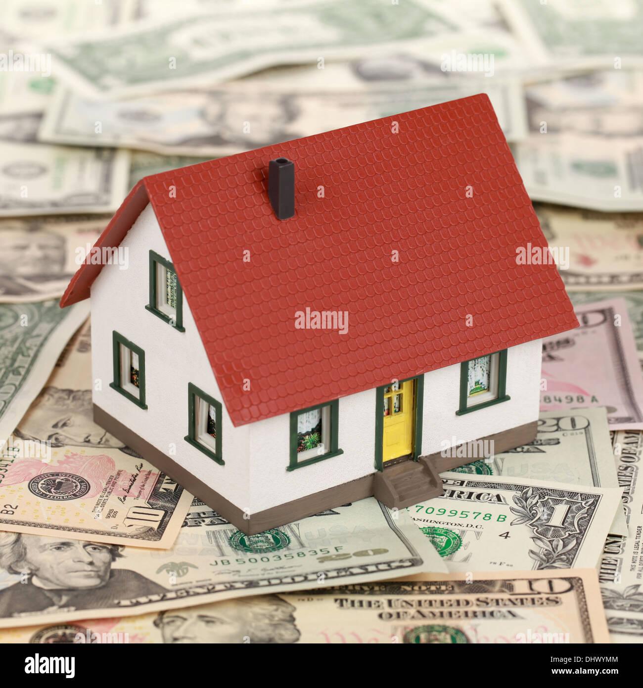 Finanzierung von Immobilien mit einem Musterhaus auf Dollar-Banknoten Stockbild
