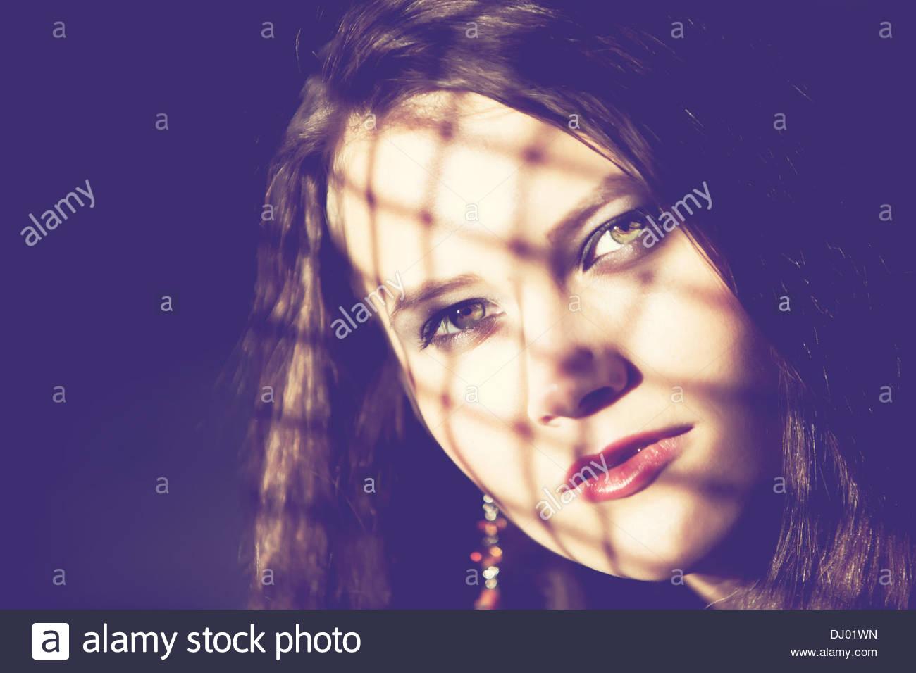 Frau, beleuchtet von der Sonne durch ein Netz Stockbild