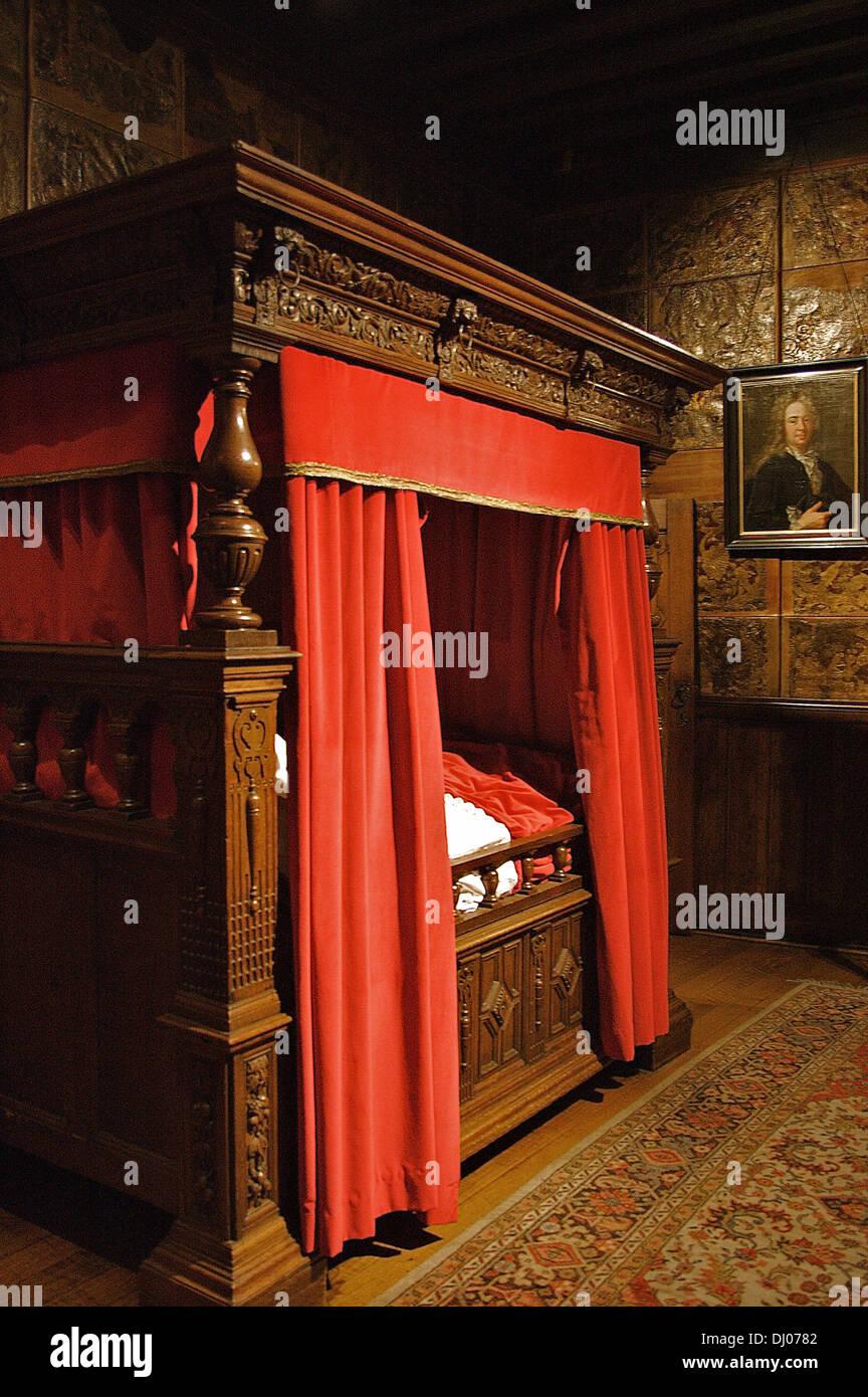 Ein geschnitzter Eiche Bett in einem Zimmer mit vergoldetem Leder ...