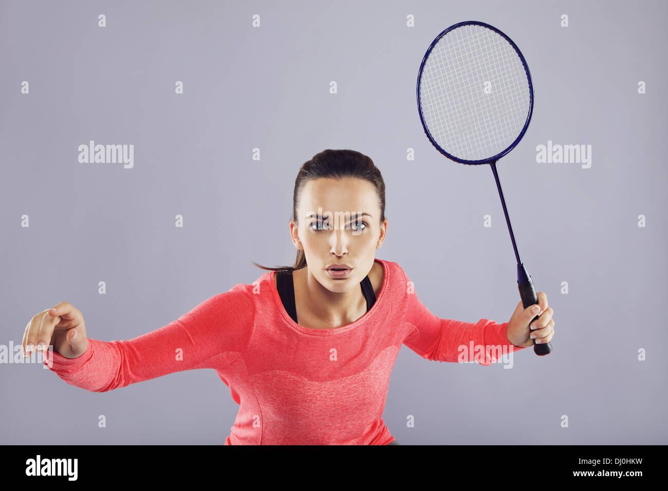 ddd551f0e7541e Porträt der jungen Sport Frau spielt Badminton vor grauem Hintergrund.  Passen Sie Sportler Badminton spielen.