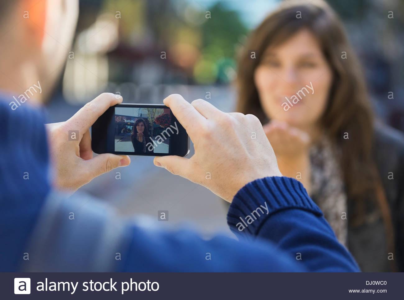 Mann zeigt Foto von Frau weht Kuss auf Smartphone Stockbild