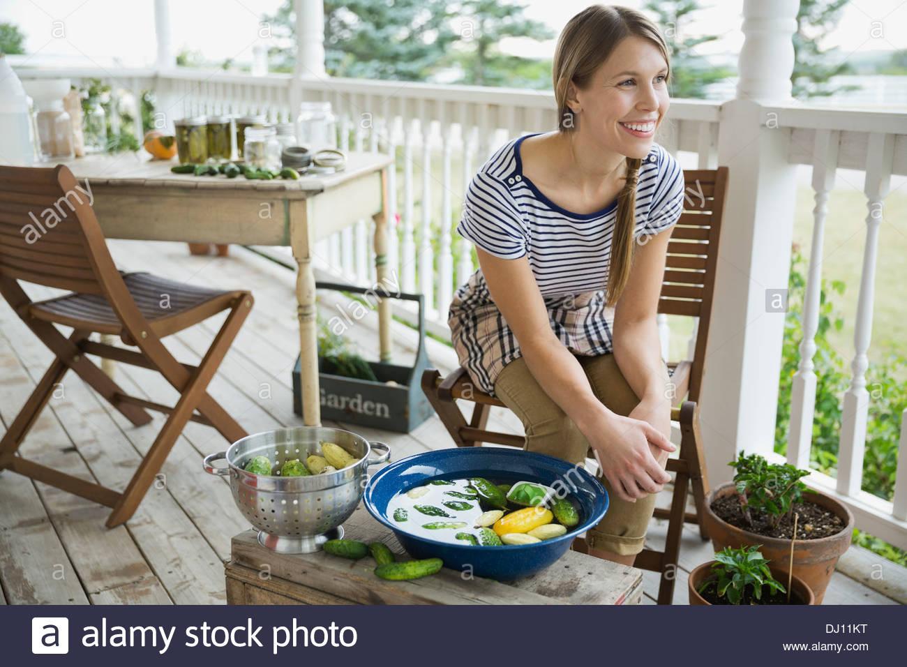 Frau waschen Gemüse auf Veranda Stockbild