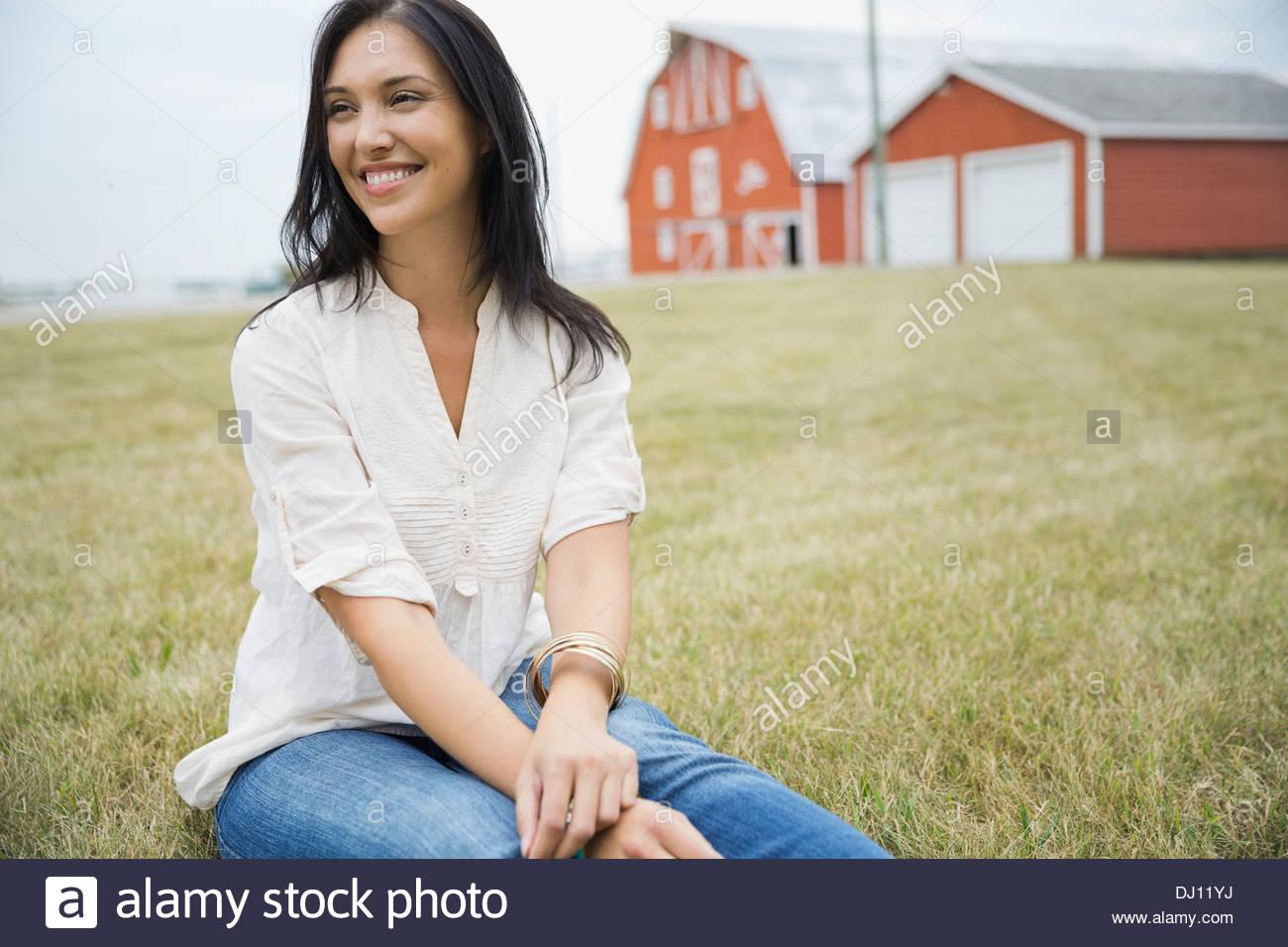 Lächelnde Frau sitzen im freien Stockbild