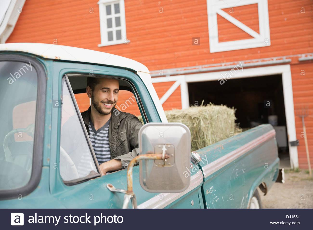 Glücklicher Mann Pick-up LKW beladen mit Heuballen Stockbild
