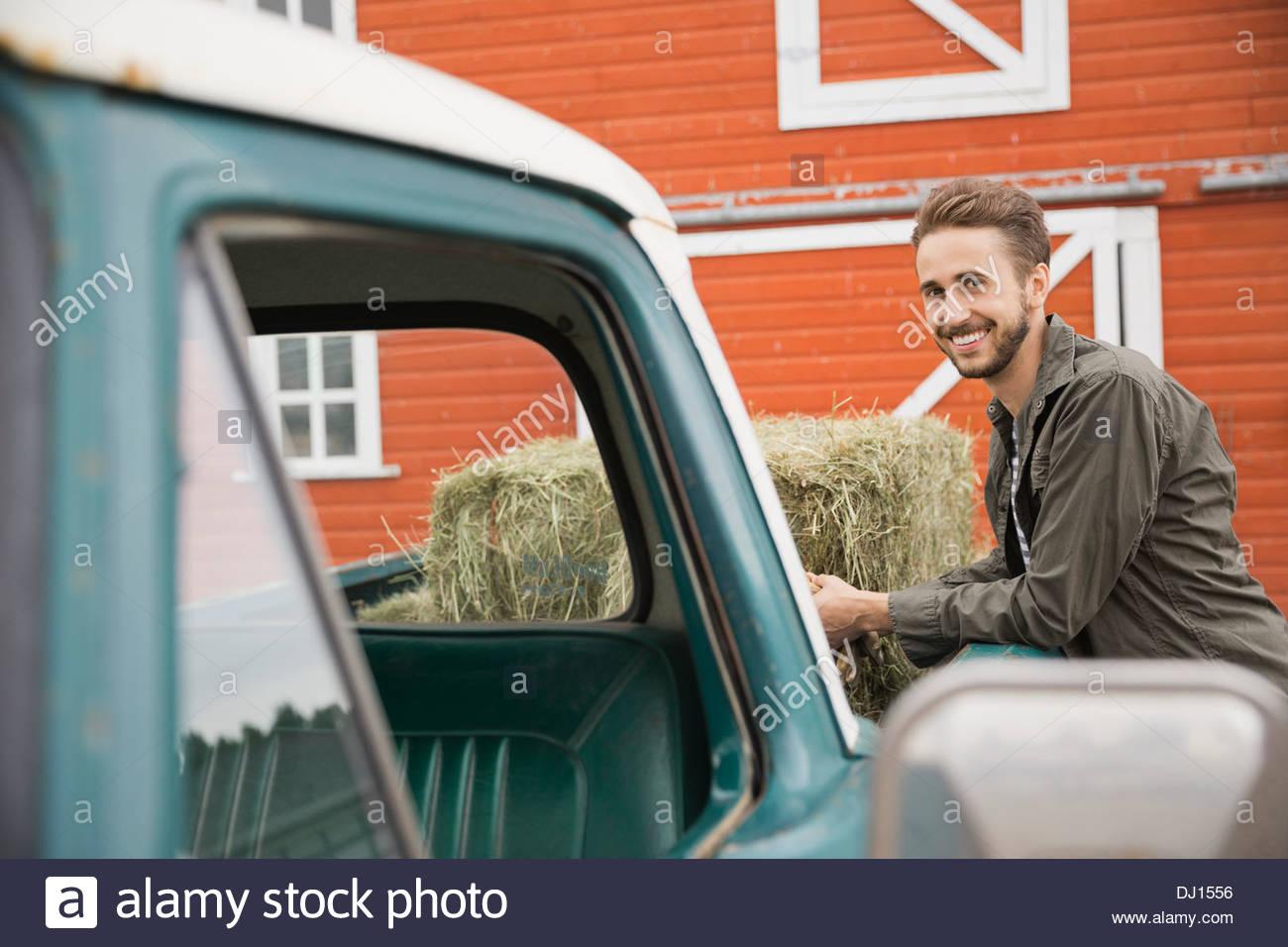 Porträt von glücklicher Mann stützte sich auf Pick-up-Truck beladen mit Heuballen Stockbild