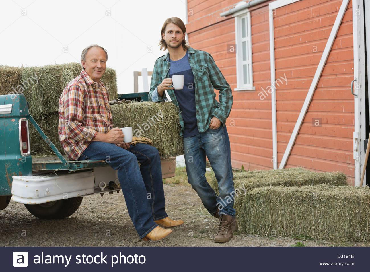 Vater und Sohn Kaffeetrinken von Pick-up-Truck mit Heuballen Stockbild