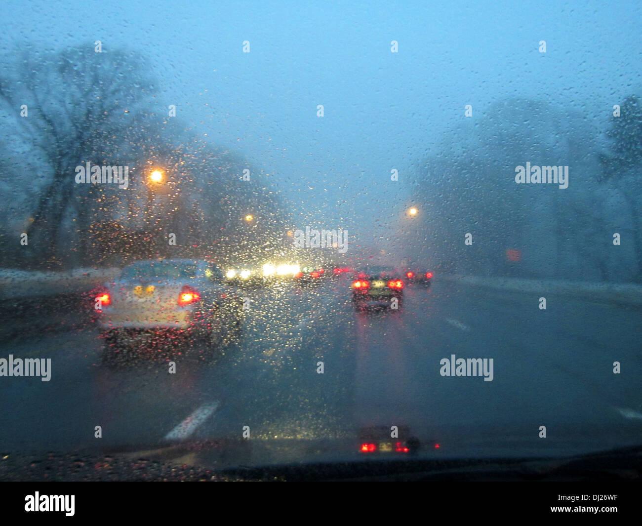 Fahren auf einer Landstraße in der Abenddämmerung im Feierabendverkehr mit Regen und Nebel auf der Windschutzscheibe zu sammeln. Stockbild