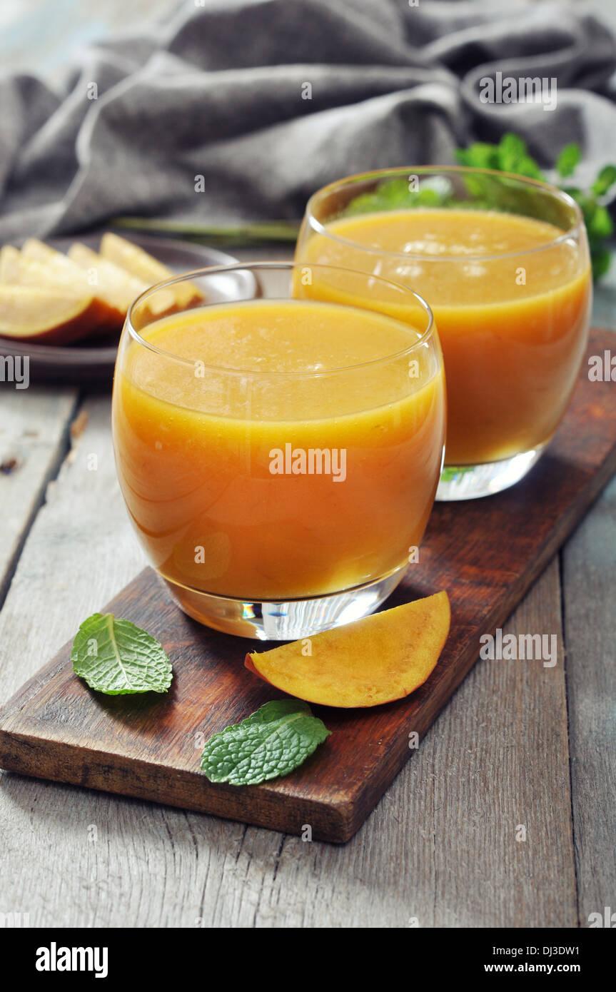 Mango Smoothie aus Glas mit Minze auf hölzernen Hintergrund Stockbild