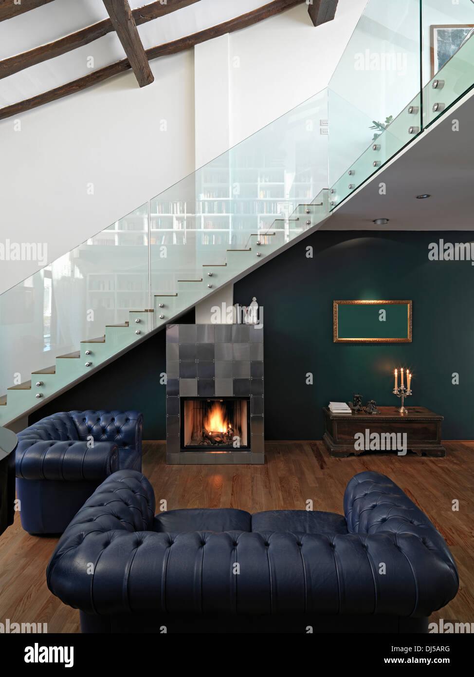moderne Wohnzimmer im Dachgeschoss mit Kamin, Holzboden und Treppe ...