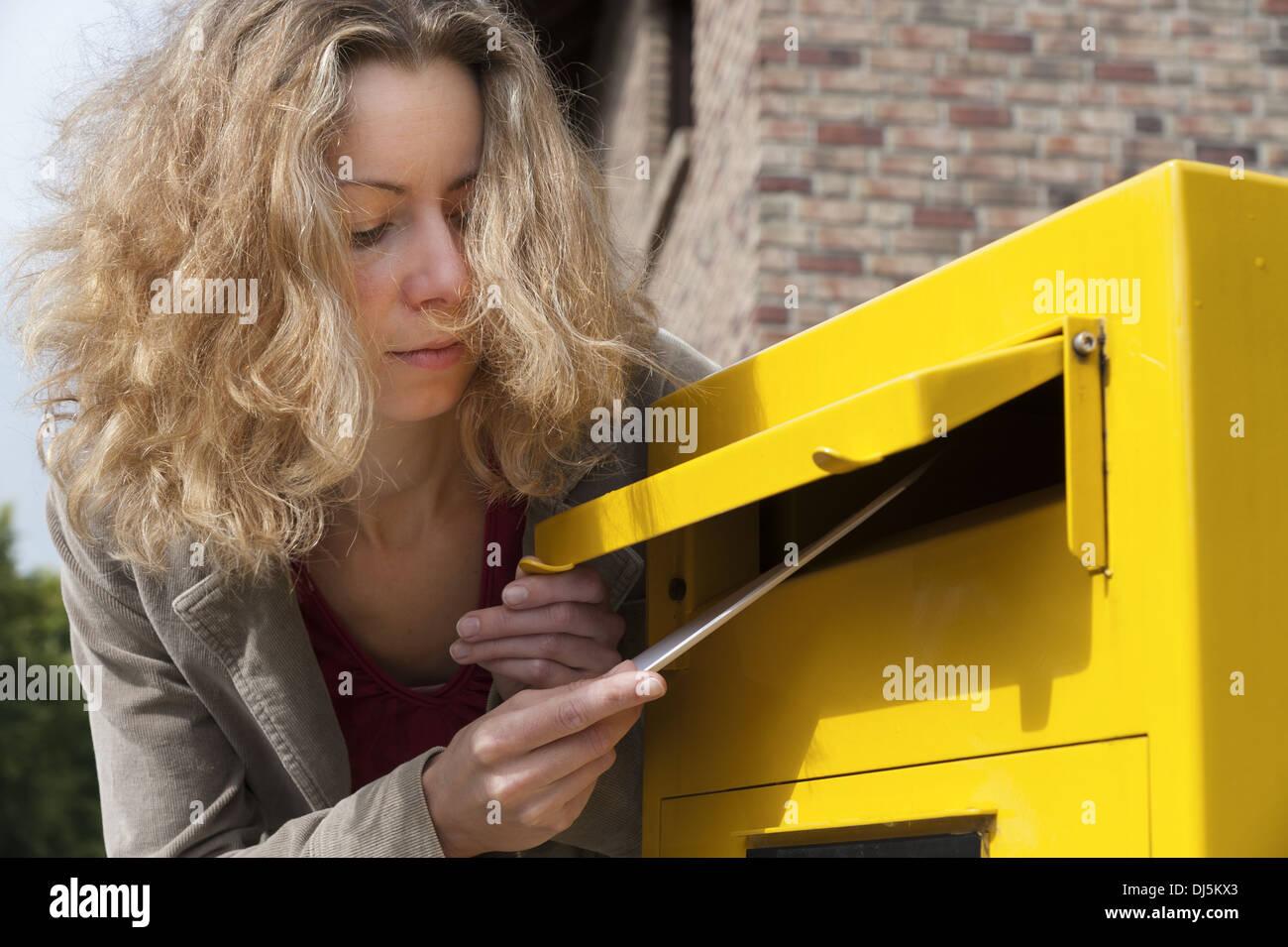 junge Frau mit einem Brief an ein Postfach Stockbild