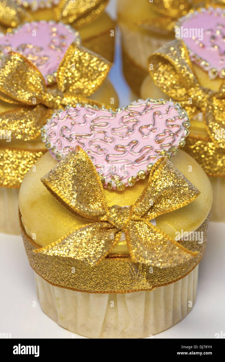 Geeiste Tasse Kuchen verziert mit rosa Herzen und goldenen Bögen. Stockfoto
