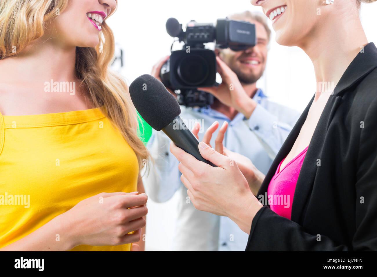 Reporter und Kameramann Film schießen Schauspielerin Interview am Filmset für TV oder Fernsehen Stockbild