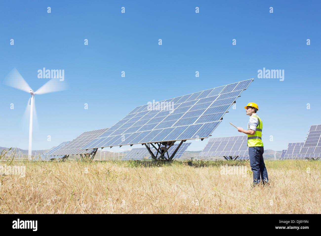 Arbeiter, die Prüfung von Sonnenkollektoren in ländlichen Landschaft Stockbild