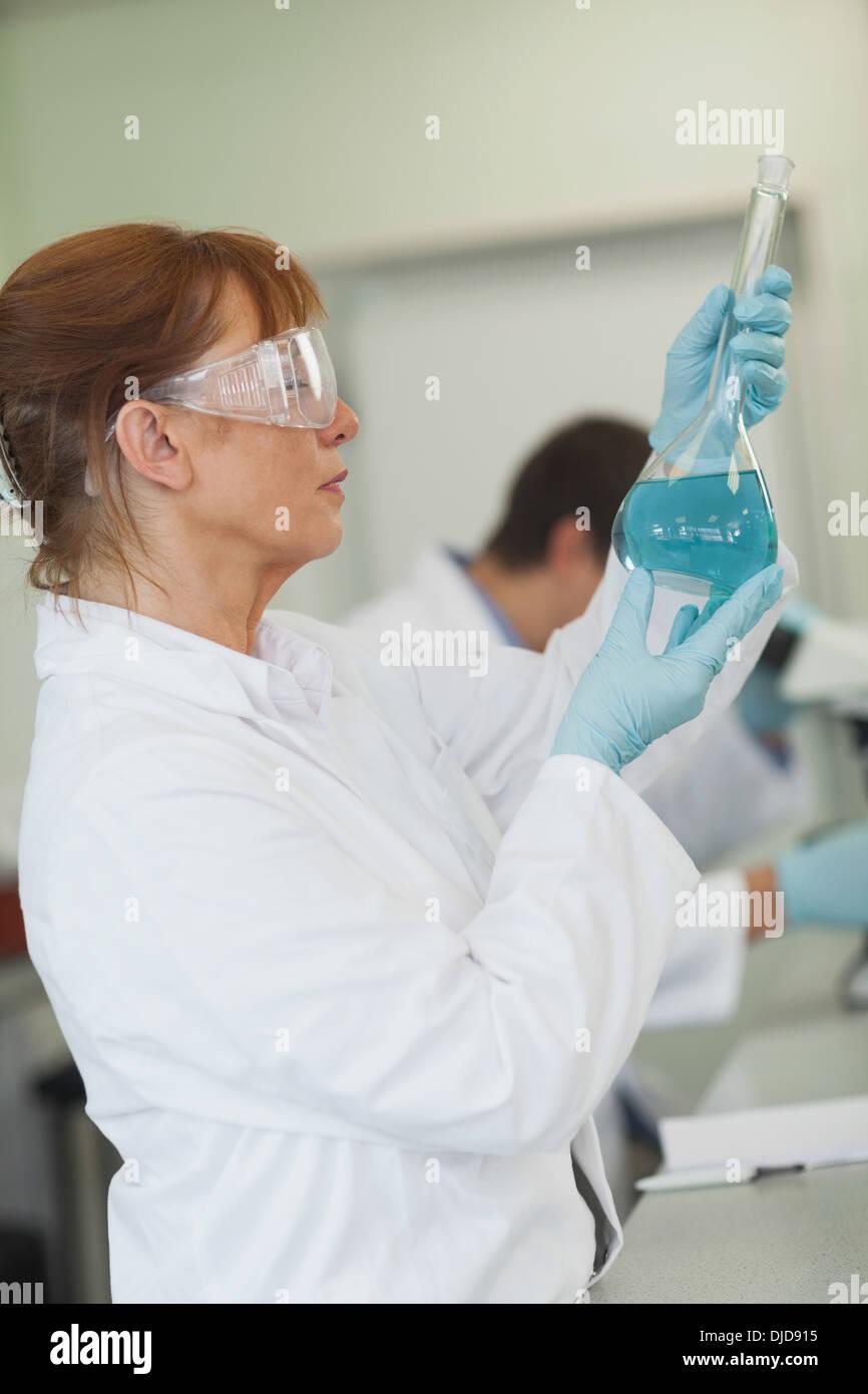 Wissenschaftlerin hält einen Erlenmeyerkolben Stockbild