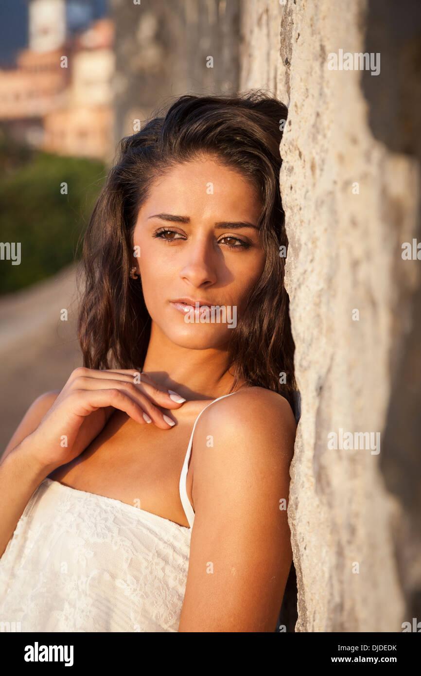 Kopfschuss attraktiven Mädchen mit dunklen Teint und langen Haaren, einem Sandstein Felsen gelehnt Stockbild