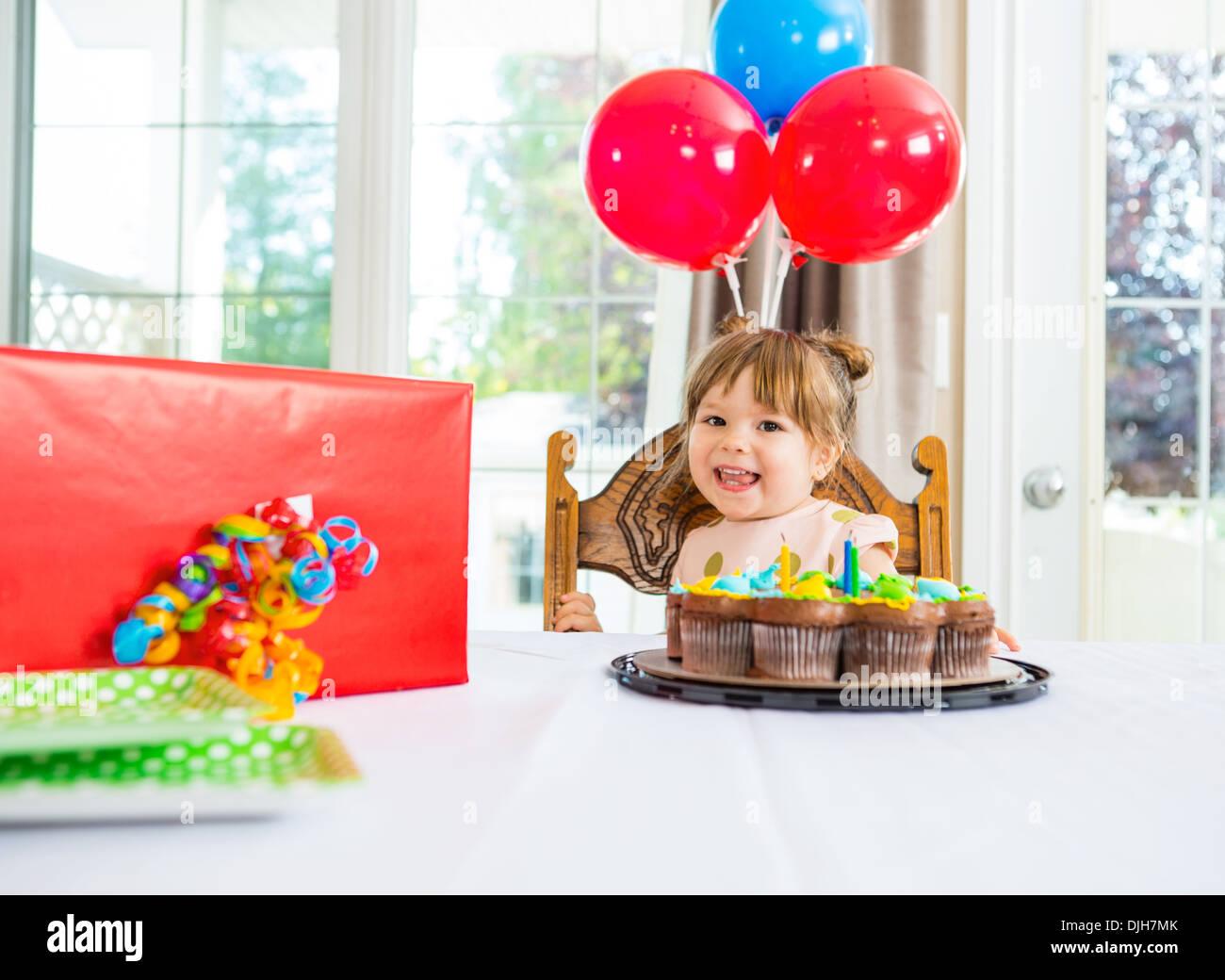 Geburtstagskind mit Kuchen und Gegenwart auf Tisch Stockbild