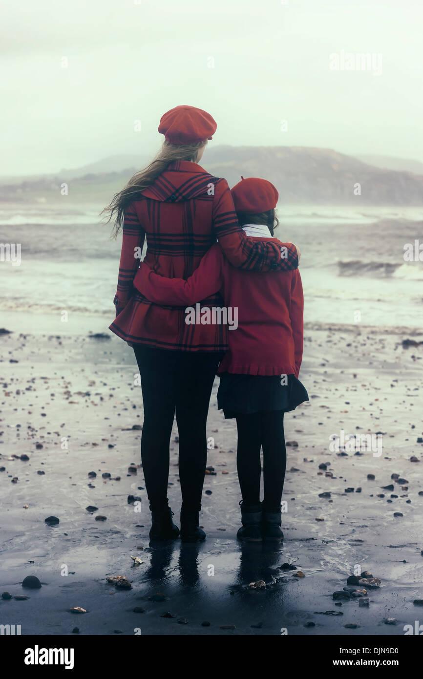 zwei Mädchen Arm in Arm am Meer Stockbild