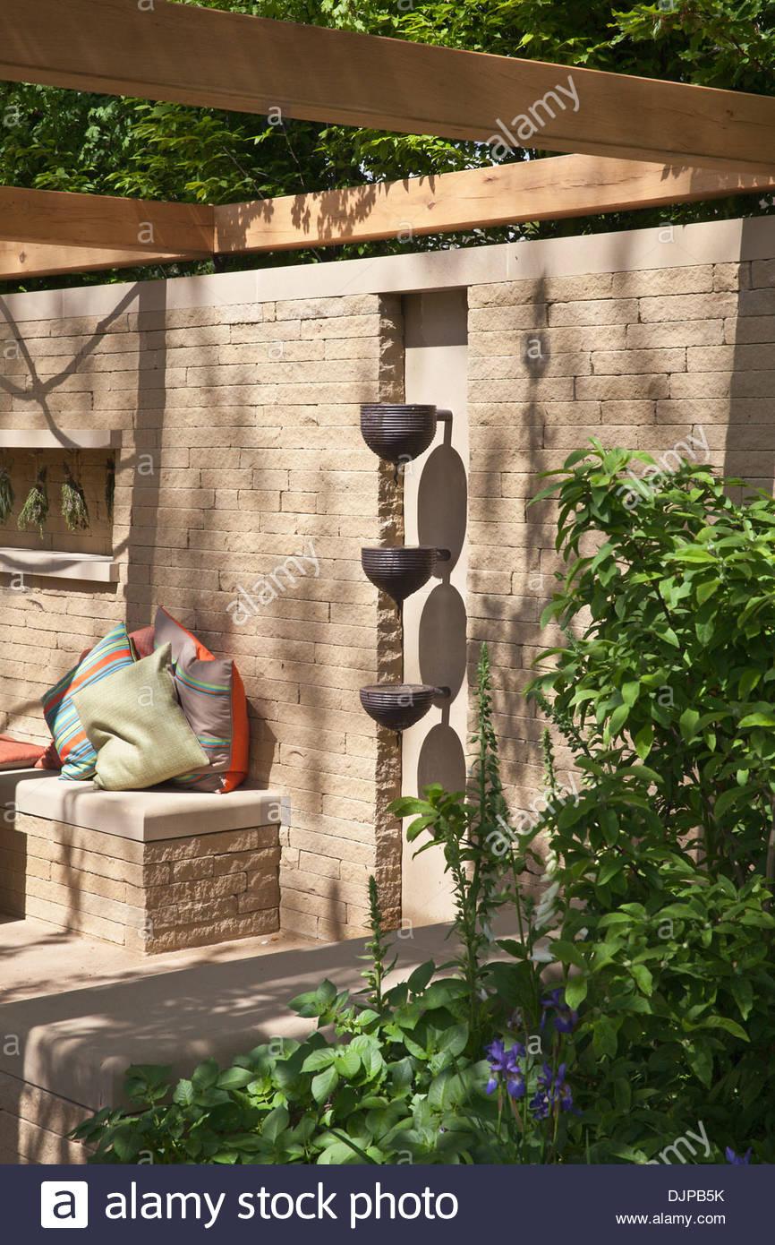 Sitzecke mit Pergola und zeitgenössische Wasserspiel auf eine Mauer ...