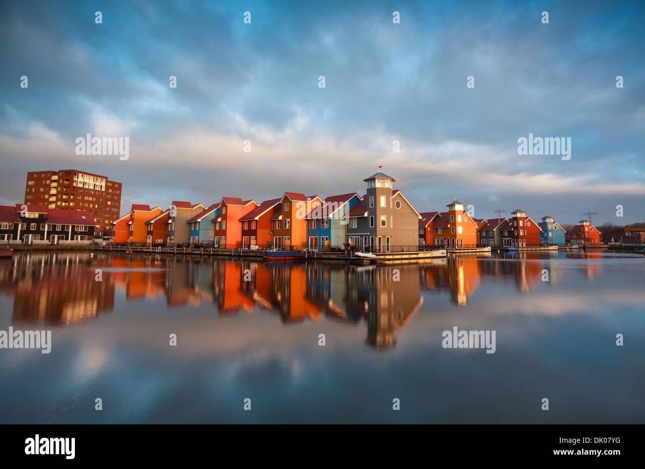 bunte Gebäude auf dem Wasser bei Sonnenaufgang, Reitdiephaven, Groningen, Niederlande Stockbild