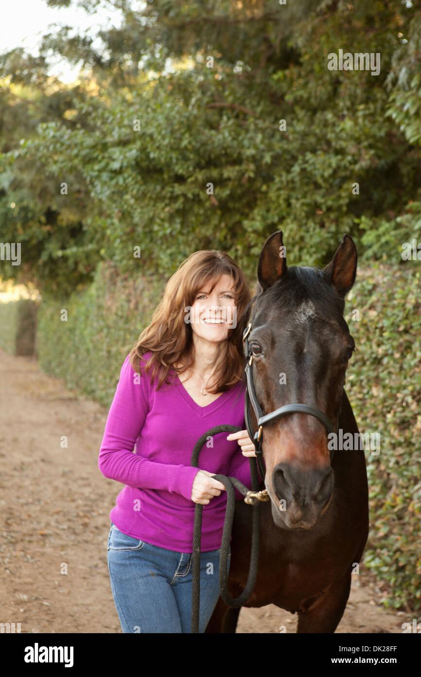 Porträt der lächelnde Brünette Frau in lila Pullover mit braunen Pferd Weg Stockbild