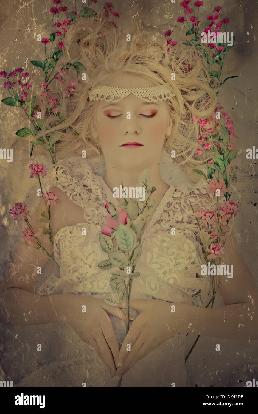 Schöne blonde Frau in weißen Spitzen Kleid mit Blumen gestreut um ihr schlafen Stockbild