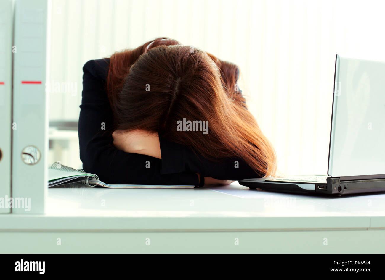 Junge müde Geschäftsfrau, die an ihrem Arbeitsplatz im Büro schlafen Stockbild