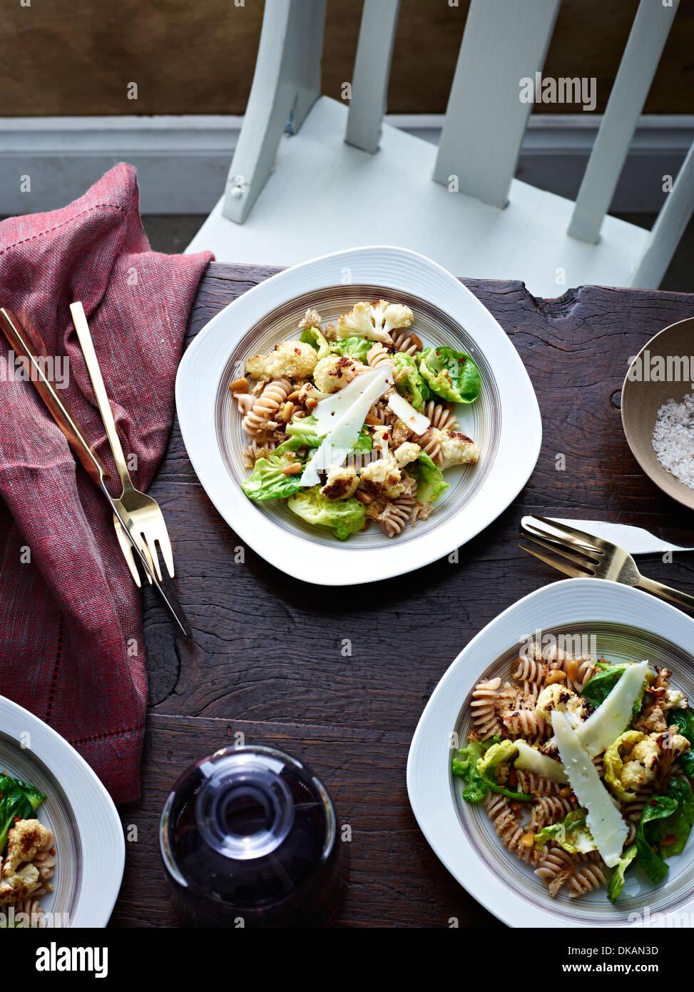Tabelle mit Blumenkohl-Pasta und Parmesan-Scheiben Stockbild